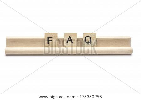 Abbreviation of FAQ on scrabble wooden letters on a rack isolated on white background
