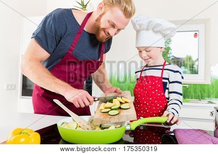 Father and son preparing food together in kitchen