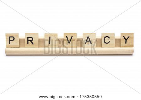 Word ''privacy'' on scrabble wooden letters on a rack, isolated on white background