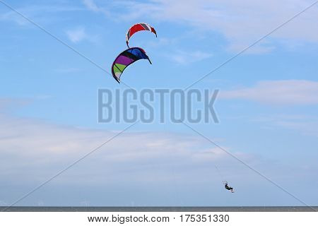 kitesurfer jumping on his board from the sea