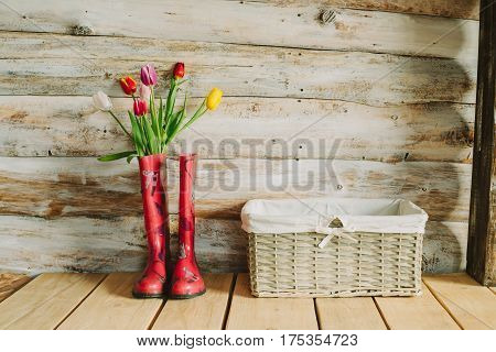 colorful rain boots with spring flowers in wooden background.