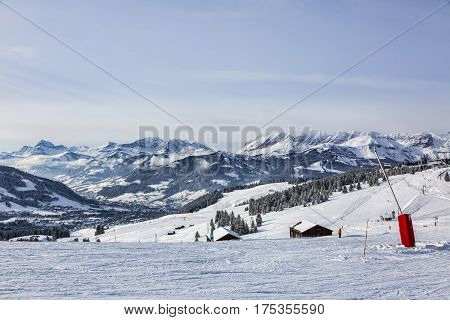 Empty ski domain located at high altitude in Alps in Beaufortain Massif in Haute-Savoie close to Mont Blanc. In the distance can be seen Chaine des Aravis above the clouds and villages.