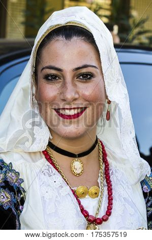 QUARTU S.E., ITALY - September 17, 2016: Parade of Sardinian costumes and floats for the grape festival in honor of the celebration of St. Helena. - Portrait of a beautiful smiling woman in traditional Sardinian costume - Sardinia