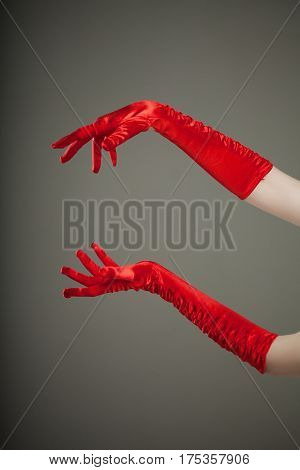 Elegant empty open female hands in red silk or satin gloves, free space presenting your product or text