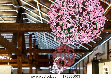 Pinl Flowered Chandeliers Hang From A Wooden Wall