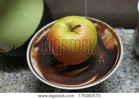 appetizing green sweet apple lay on  porcelain saucer with chocolate abstract ornament