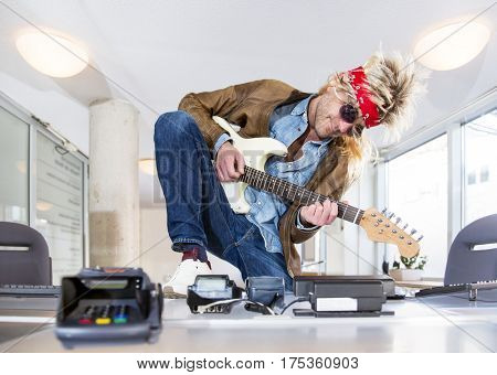 Rockstar at a ticket booth playing a guitar, selling tickets for a rock event or concert at a theater