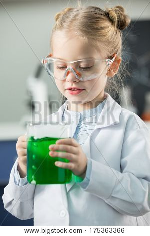 Little girl wearing lab coat and protective glasses holding flask with green reagent