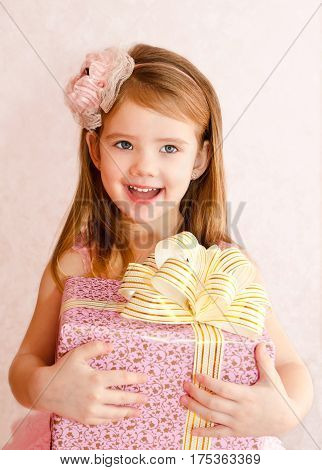 Adorable little girl in princess dress holding the gift box isolated