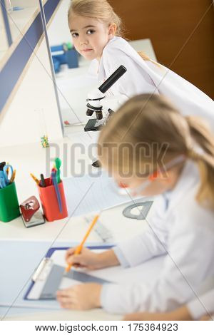 Schoolchildren in white lab coats studying together and making notes in lab
