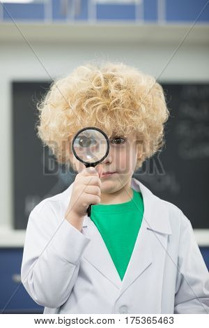 Cute schoolboy in lab coat holding magnifying glass