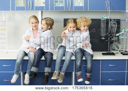 Schoolchildren in lab coats sitting together in chemical laboratory