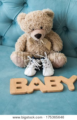 Tiny baby shoes and teddy bear on the blue sofa in baby's room and wooden sign baby