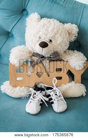 Tiny baby shoes and white teddy bear on the blue sofa in baby's room and wooden sign baby
