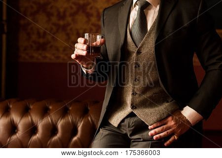 Groom holds in his hand a glass of whiskey indoors. Stylish man's hand with a ring on the little finger