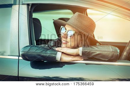 Woman at spreeng time. Yoyng happines female in hat and sunglasses sitting in her black car at sunny day.
