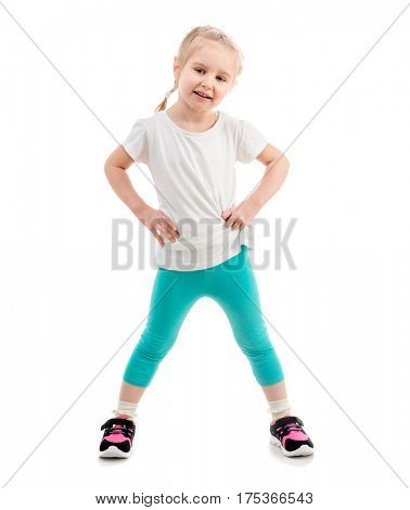 Sweet child in sportswear in a wide stance smiling widely, isolated on white background