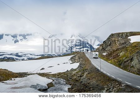 Motorbike and camper van are traveling the famous County Road 55. Highest mountain road in Norway, part of National Tourist Route.