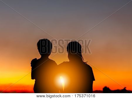 Silhouette of Mother and Son Watched Together at Sunset Evening Sky Background Life and Happiness family Concept.