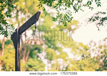 simple basic lamp on old rustic wooden lamppost against blurred trees and sky background vintage cinematic color tone room for copyspace