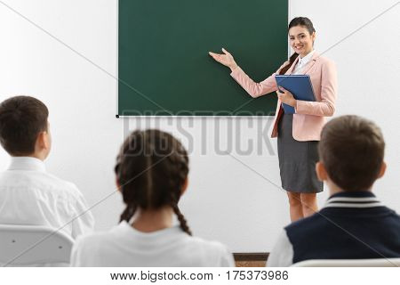 Teacher explaining new topic while standing near blackboard in classroom