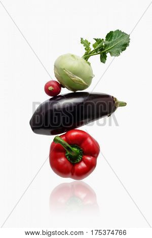 A stack of vegetables: eggplant, pepper, kohlrabi and radish. Vegetables arranged in a stack.