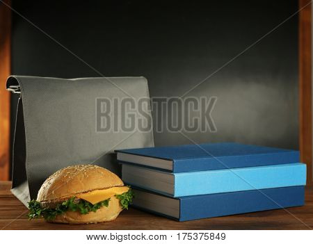 Modern lunch bag, hamburger and books on wooden table against blackboard background