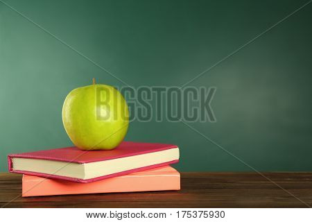 Appetizing green apple and books on wooden table against blackboard background
