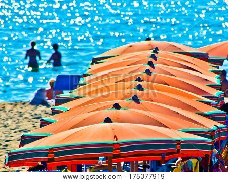 bathers on vacation on the sea background with orange umbrellas in summer with blue sky