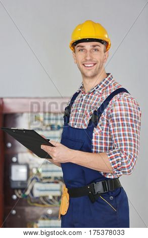 Young electrician with clipboard standing near open distribution board