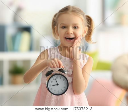 Cute little girl with alarm clock at home