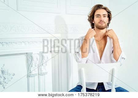 Handsome sexy man wearing white shirt looking at camera. Men's beauty, fashion model. Hair styling.