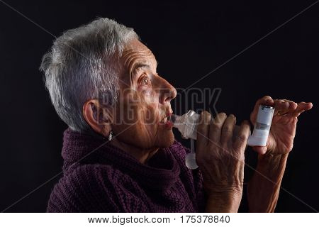 Senior woman with inhaler on a white background