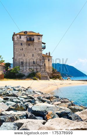 Ancient Ouranoupolis Tower on Athos peninsula in Halkidiki, Greece, Pier, sea shore and Aegean sea water
