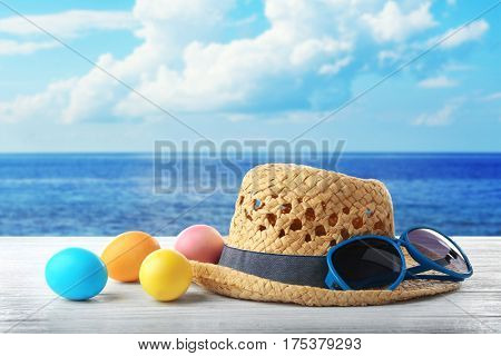 Easter eggs with hat and sunglasses on wooden table at shore