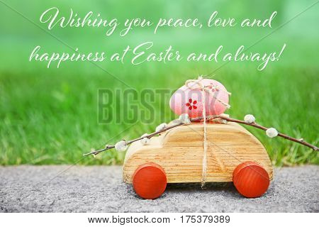 Greeting card design. Wooden toy car with pussy willow and Easter egg on grass background