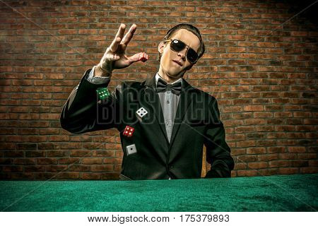 Excited gambling man throwing dice on a game table in a casino. Gambling, playing cards and roulette.