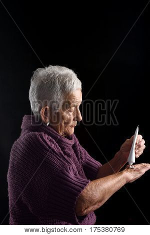 Senior woman with ointment on a black background