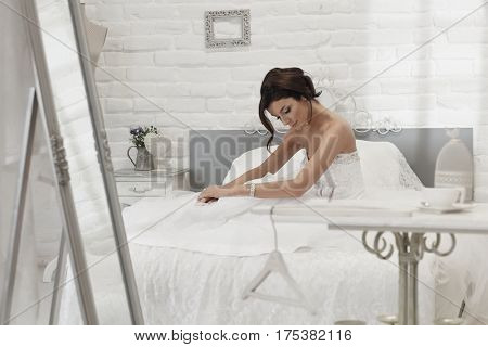 Bride sitting on white bed in white bedroom.