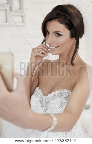 Beautiful young bride making selfie by mobilephone.