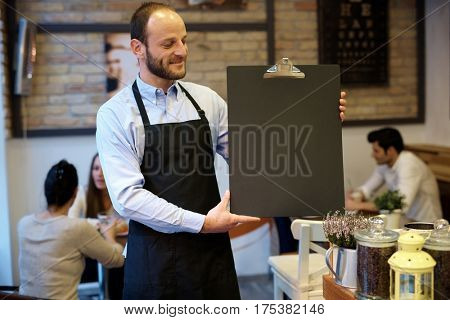 Waiter holding blackboard with blank space, smiling.