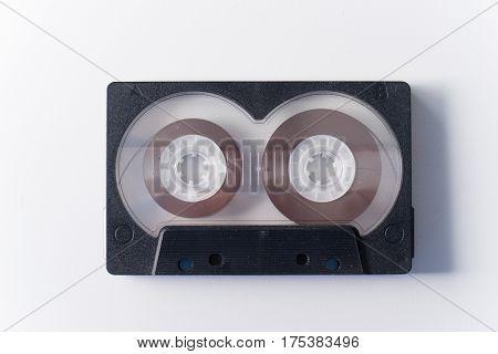 One black audio cassette on white background.