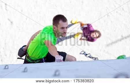 Male Athlete moving up on vertical climbing Wall and his belaying Partner staying on Background. National Climbing Championship, Dnipro, Ukraine, May 20, 2016, Male semifinal, Lead climbing