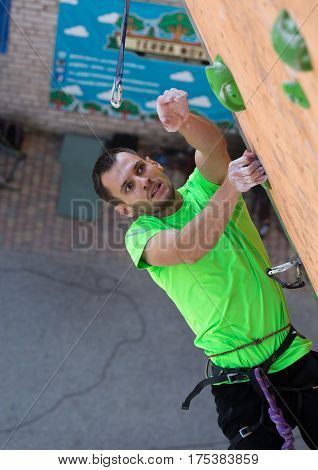 Male Climber trying to reach a hold on Climbing Wall. National Climbing Championship, Dnipro, Ukraine, May 20, 2016, Male semifinal, Lead climbing