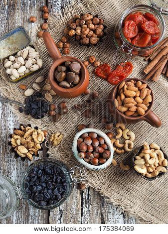 Various nuts and dried fruits - cashew, walnut, pistachios, hazelnuts, dried apricots, raisins,  in bowls and jars on burlap on a wooden table