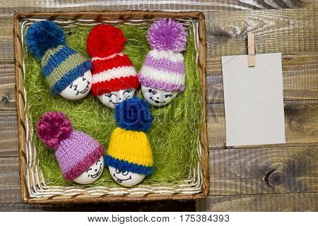 Easter Eggs On Green Sisal. Emoticons In Knitted Hat With Pom-poms.