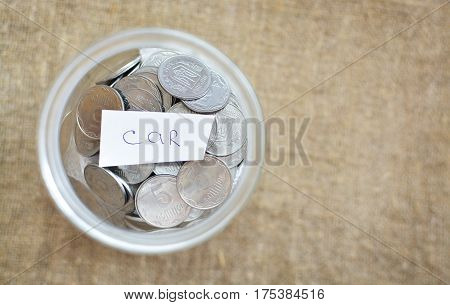 Glass Jar Filled With Coins Labeled With The Words Of The Car. View From Above. Background Of Burlap