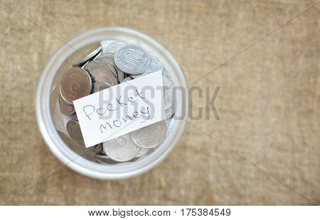 Glass Jar Filled With Coins Labeled With The Words Of Pocket Money. View From Above. Background Of B