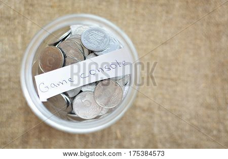 Glass Jar Filled With Coins Labeled With The Words Video Game Console. View From Above. Background O