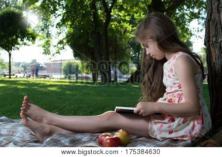 Cute Little Girl In A Dress With Flowers Sitting On The Grass And Reading A Book On A Sunny Summer D